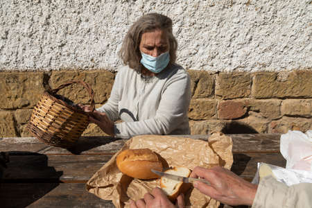 A senior adult woman, wearing a face mask, chooses the amount of bread she wants, before eating at the mountain hut of the fountain of Artica, in Luesia, Spain.