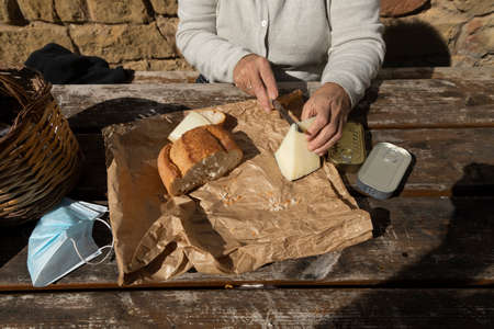 A senior woman, cuts slices of goat cheese at the mountain hut of the fountain of Artica, in Luesia, Spain.