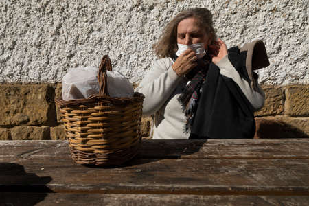 A senior woman, with short hair, sitting at the table in front of the mountain hut of the fountain of Artica, in Luesia, Spain, correctly adjusts her protective face mask.