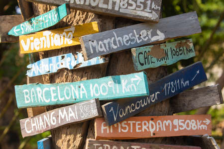 Colorful hand painted direction wood signs to different cities of the world, and mileage marker in Don Det island, one of the famous Four Thousand Islands or Si Phan Don, in the Mekong river, Laos.