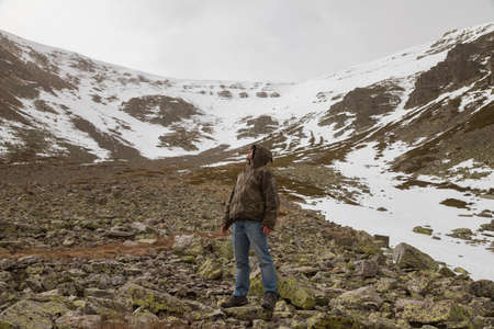 Stock photo of a man wearing camouflage clothing, and trekking in the high mountain of Moncayo in Aragon, Spain, surrounded by huge rocky and snowy hillside.