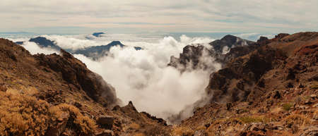 Impressive panoramic landscape of clouds and volcanic mountains from the top of the Roque de los Muchachos viewpoint, on the island of La Palma, Canary Islands, Spain.
