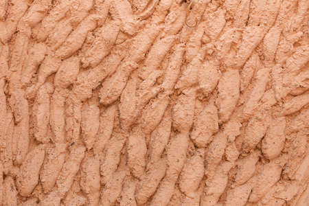 Photography of texture and background of a facade arranged with cement and painted salmon pink, in a house in Ambel, a small town in the Campo de Borja region, Zaragoza, Aragon, Spain.