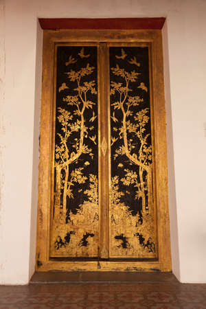 Bangkok, Thailand - March 25, 2018: Huge golden door in Phutthaisawan Hall, decorated with sumptuous plant motifs, in the grounds of the Bangkok National Museum, an example of Thai architecture. Editoriali