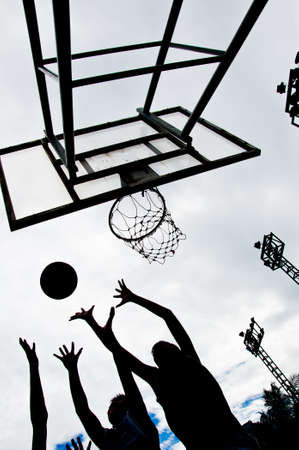 Silhouette of boys making a basketball dunk photo
