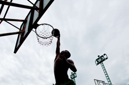 Silhouette of a boy making a basketball dunk