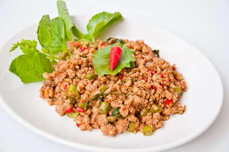 맛있는 태국 음식 호출 PUD KAPRAO MOO 매운 성분의 고추, 마늘, 긴 콩, 생선 소스와 함께 튀긴 된 돼지 고기에서 만든 바질 쌀을 먹고