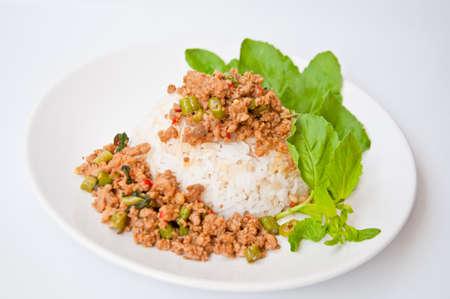 â        image: Deliciosa comida tailandesa llamada KHAO KAPRAO MOO hecha de carne de cerdo frita con ají ingrediente picante, ajo, frijol largo, salsa de pescado, la albahaca Foto de archivo