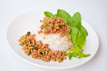 Delicious Thai food call KHAO KAPRAO MOO made from fried pork with spicy ingredient chili ,garlic,long bean,fish sauce, basil  Stock Photo - 10901342