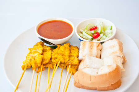 Delicious Thai food call  MOO SATAE for appetizer made from grill pork eat with bread and soup and chili and cucumber in vinegar photo