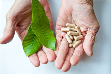 Pill and leaf on old woman hand for good health photo