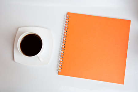 black coffee and orange notebook on white background photo