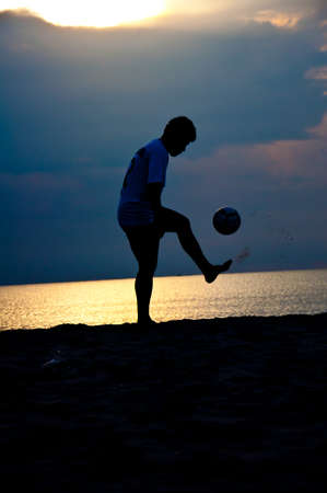 silhouette of man playing soccer on the beach Stock Photo