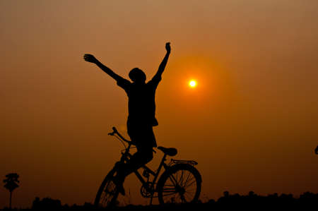 silhouette of boy happy with bicycle photo