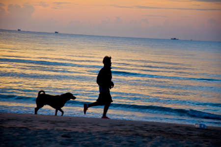 silhouette of man running on the beach with dog photo