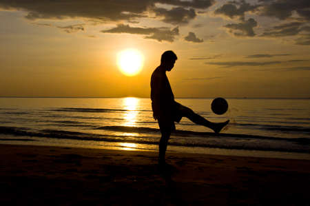 silhouette of man play soccer on the beach photo