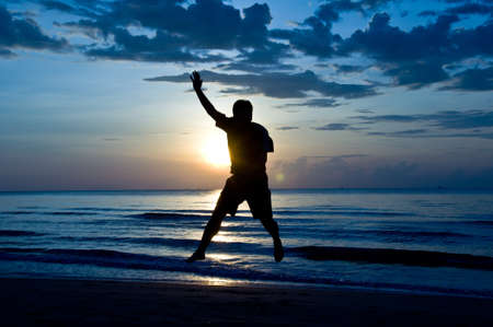 silhouette of man feel free and happy on the beach photo