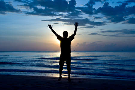 silhouette of feel free and happy man on the beach photo