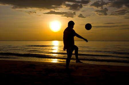 silhouette of man play soccer on the beach