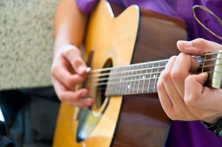 fretboard: hand for play guitar from children hand Stock Photo