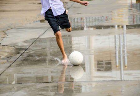 children play soccer with barefoot and raining photo