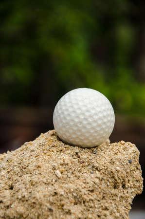 white golf ball on   sand