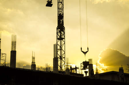 crane: silhouette of worker working with crane for construction