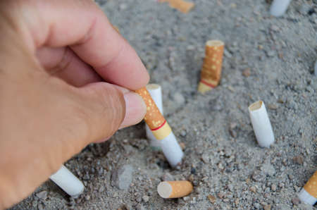ciggy: hand for leave ciggarette on sand Stock Photo