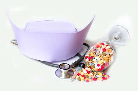 enfermera con cofia: gorra blanca para la enfermera en el fondo blanco y una jeringa con la medicina Foto de archivo