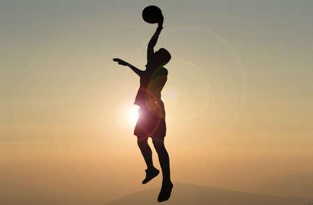 silhouette of man playing basketball