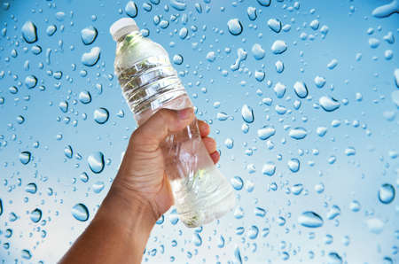hand for bottle of water on drop water background