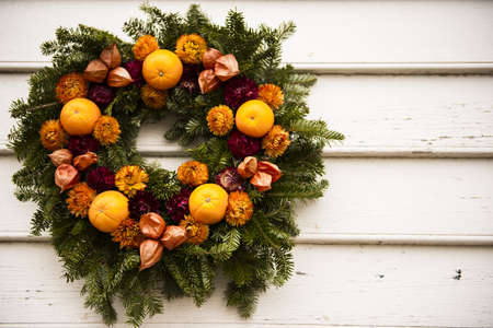 Pine wreath with oranges and carnations on wooden siding Stock fotó