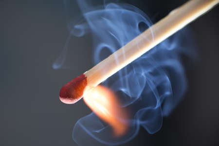 ignited: Matchstick at Moment of ignition with curling blue smoke and flame