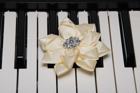 pianoforte: White flower over electronic keyboard Stock Photo