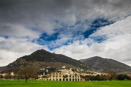 The ancient Roman theater in front of the medieval town of Gubbio photo