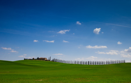 Tuscany landscape with typical farm house on a hill in Val d photo