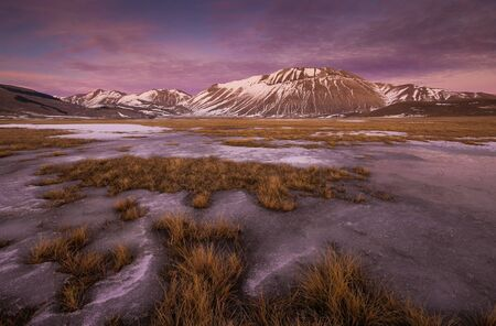 castelluccio di norcia: Beautiful sunset winter landscape with snow-covered mountain in violet and pink colors. Castelluccio di Norcia, Umbria - Italy.