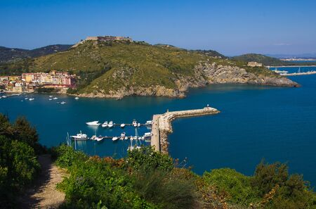Porto Ercole village and boatd in harbor in a sea bay. Filippo fort on background. Aerial view. Monte Argentario, Tuscany, Italy Zdjęcie Seryjne