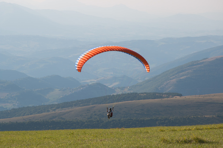 Paraglider flying over mountains in summer day Stock Photo