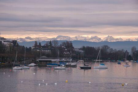 ZURICH, SWITZERLAND - DECEMBER 11, 2016: Romantic sunset on Zurich lake with alps in background