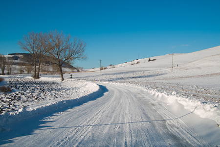 Empty snow covered road in winter landscape Stock Photo