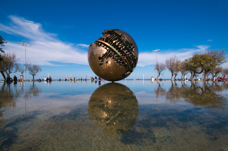 The big sphere of Arnaldo Pomodoro on the sea of Pesaro Zdjęcie Seryjne - 77216818