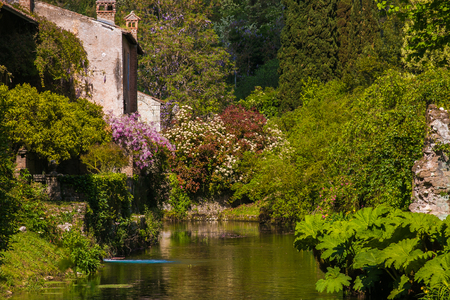 Romantic cottage with flowers on the riverside