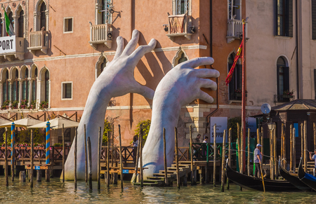 VENICE, ITALY - MAY 23, 2017: Monumental hands rise from the water in Venice to highlight climate change Publikacyjne
