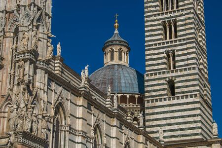 Siena Cathedral closeup with dome and statue as the famous landmark in medieval town in Italy Stock Photo