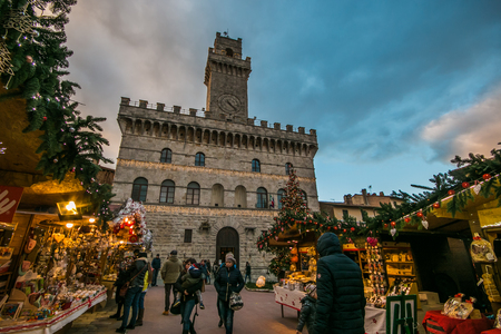 Enchanted atmosphere at the Christmas market in the historic center of Montepulciano with big xmas tree, Tuscany