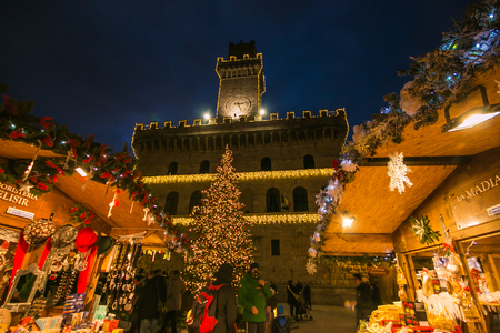 Enchanted atmosphere in the beautiful square of Montepulciano with Christmas market and tree Фото со стока