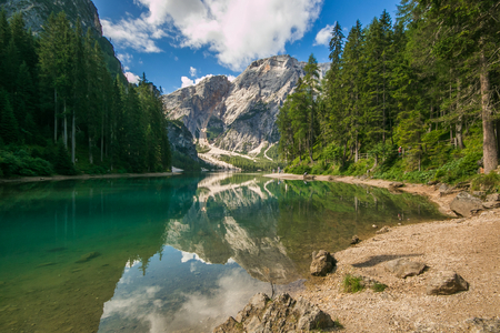 Wonderful summer scenery on Braies Lake (Lago di Braies) and larch trees with reflection in the water. Fanes-Sennes-Prags (Fanes-Sennes-Braies) Nature Park, Dolomite Alps, South Tyrol, Italy Фото со стока