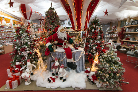 Terni, Italy - October 20, 2019: Santa Claus sitting on hot air balloon with christmas trees and decorations at the interior of christmas shop in the center of Terni