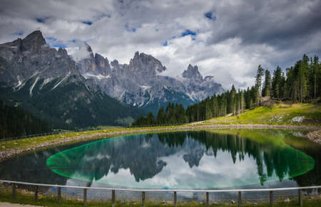 View of dolomites lake near San Martino di Castrozza during cloudy summer day, Trentino, Italy
